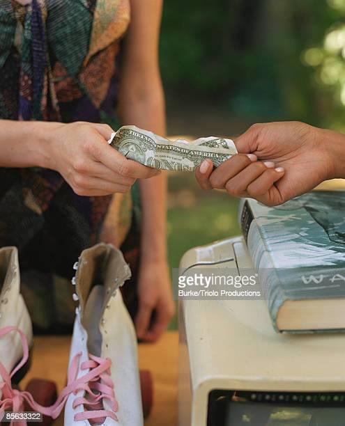 Hands of women exchanging cash for roller skates