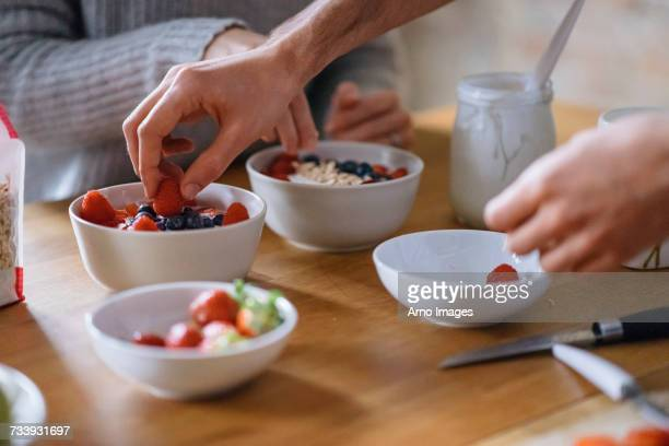 Hands of young couple preparing fruit breakfast at kitchen counter