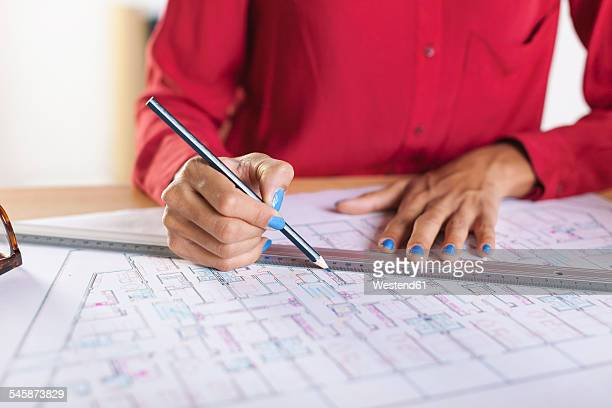 Hands of young female architect working on construction plan