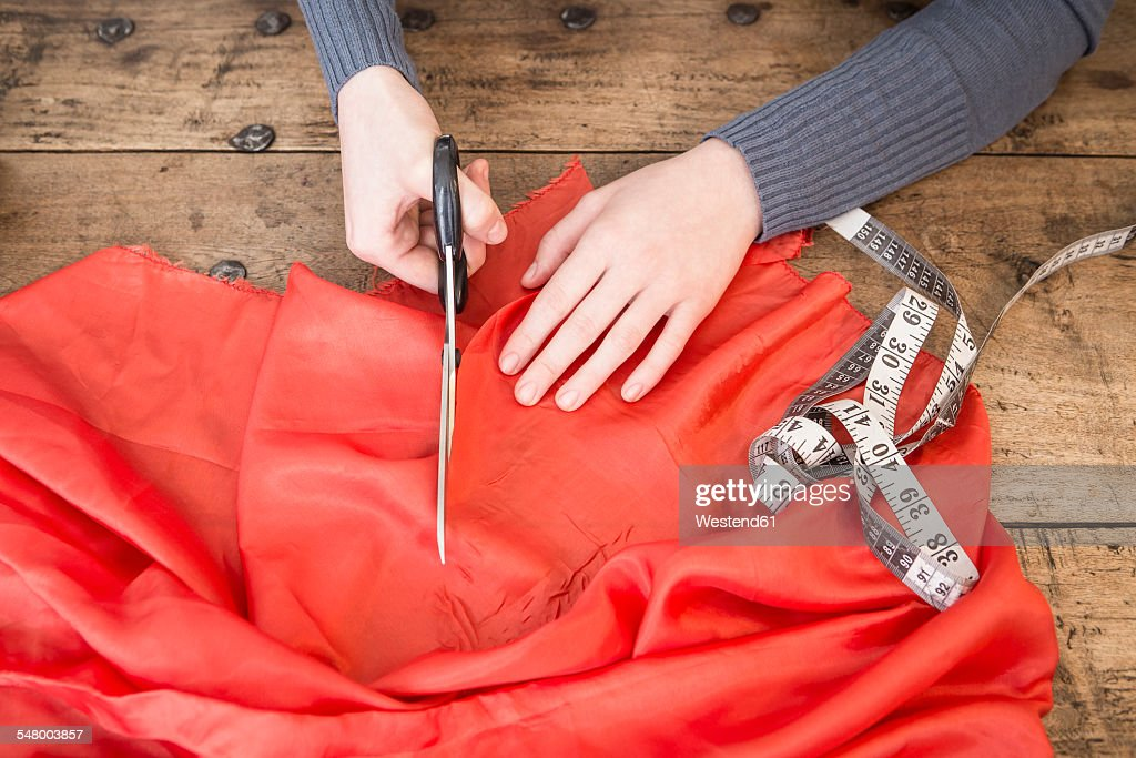 Hands of young woman cutting red cloth with scissors