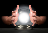A pair of male hands surrounding a crystal ball on an isolated dark studio background