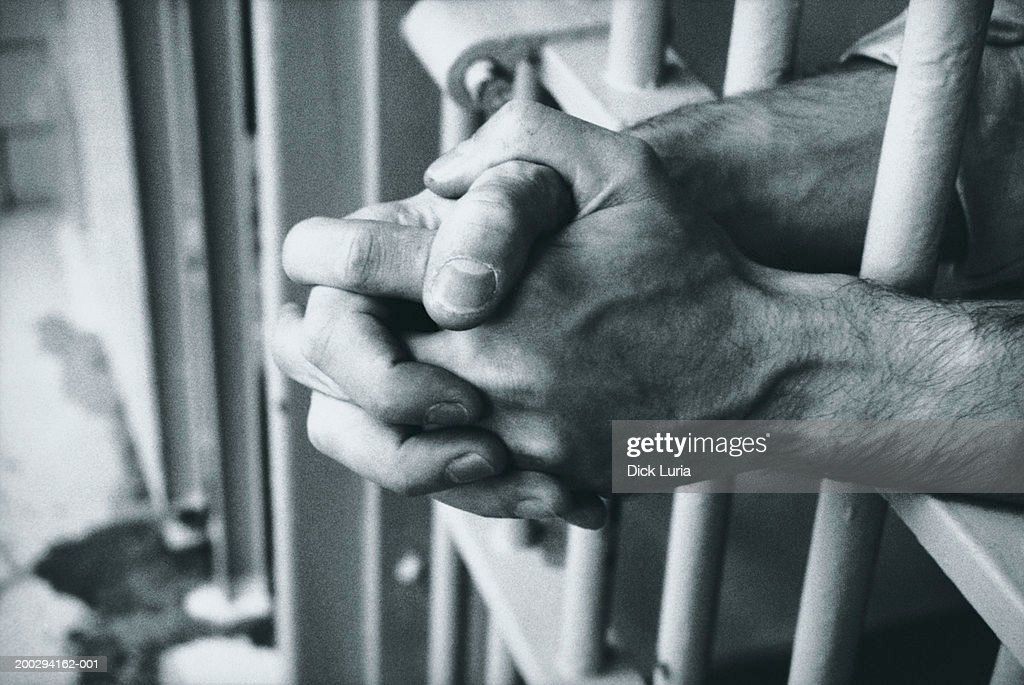 hands on prison bars : Stock Photo
