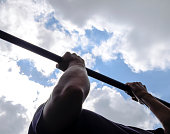 Hands on the bar close-up. The man pulls himself up on the bar. Playing sports in the fresh air. Horizontal bar