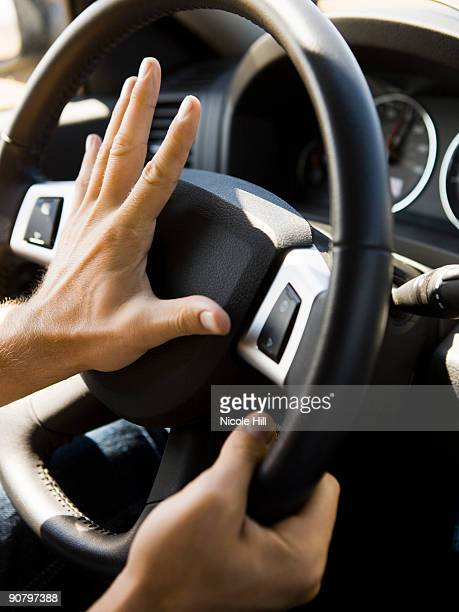 hands on the steering wheel hitting the horn