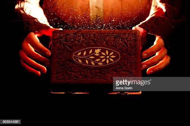 Hands opening wooden box emitting orange light