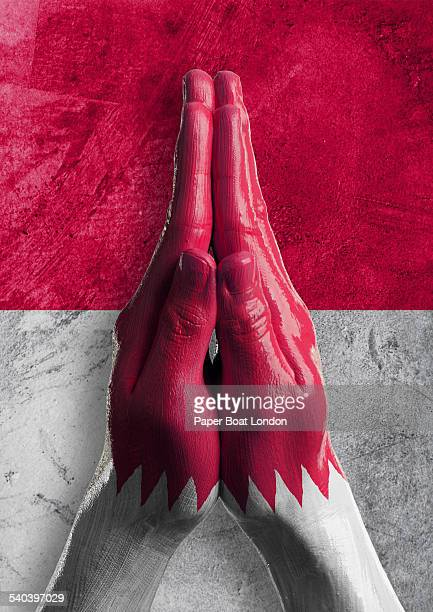 Hands painted as flag of Qatar in praying position