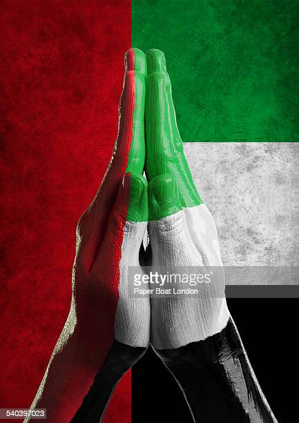 Hands painted as flag of UAE in praying position