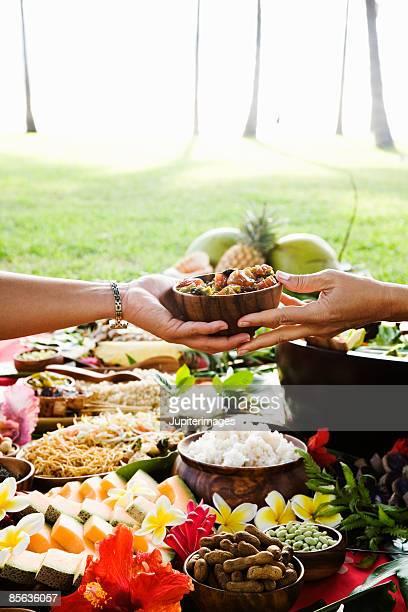 Hands passing bowl at Hawaiian picnic