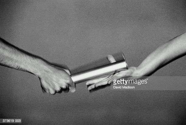 Hands passing relay baton, close-up (blurred motion, B&W)