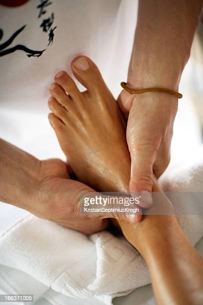 Hands perform reflexology on a foot