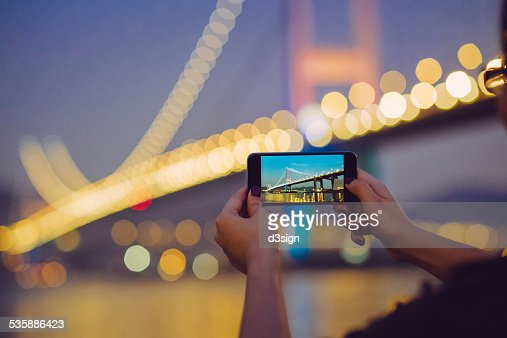 Hands photographing spectacular view by smartphone