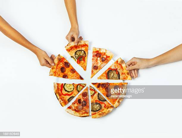 Hands picking portions of pizza