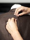 Hands pining a jacket on a dressmaker's model