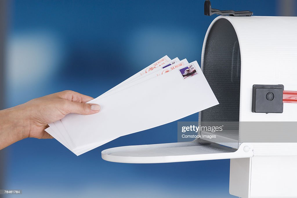 Hands placing envelopes in mailbox
