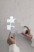Hands placing puzzle piece into jigsaw puzzle