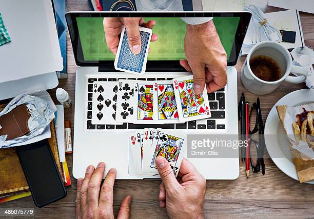 Hands playing cards through laptop screen