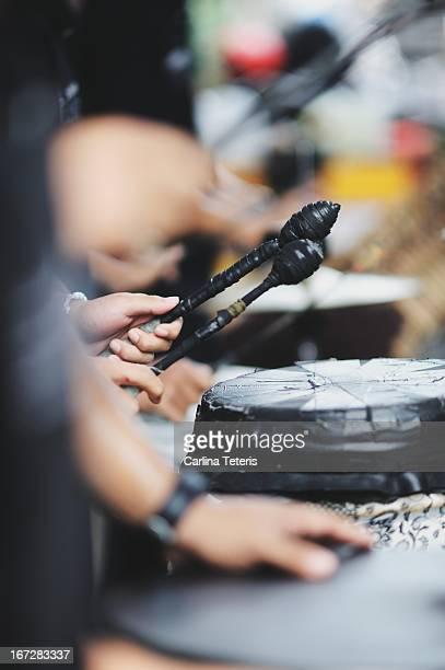 Hands playing self-made gamelan drums