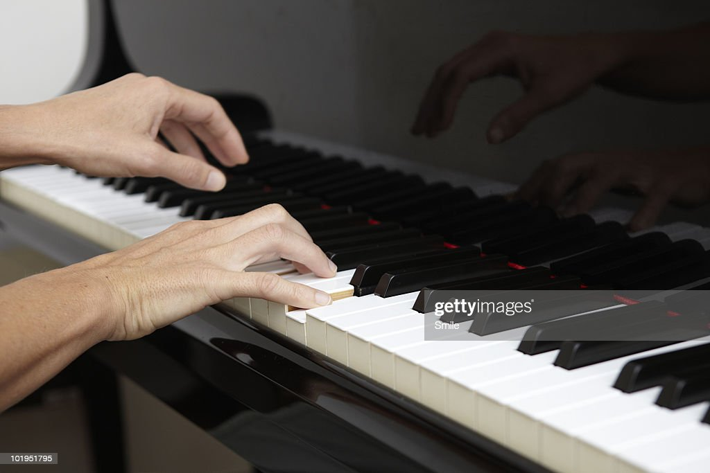 Hands playing the piano : Stock Photo
