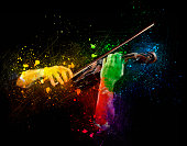 Hands playing  wooden violin on colored background