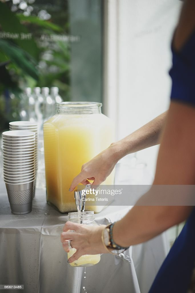 Hands pouring punch into a mason jar cup