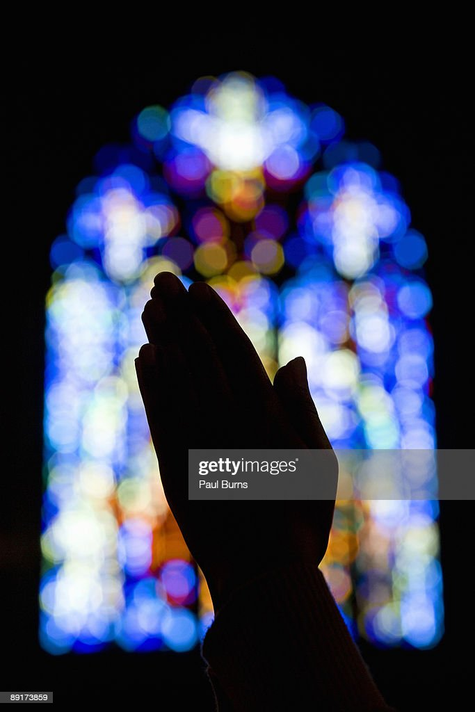 Hands Praying in Church With Stained Glass