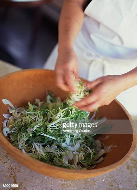Hands preparing fennel and frisee salad