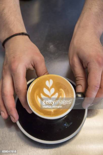 Hands presenting cappuccino with flowery pattern on milk froth