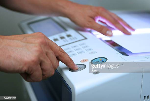Hands pressing the black-and-white button on a copy machine