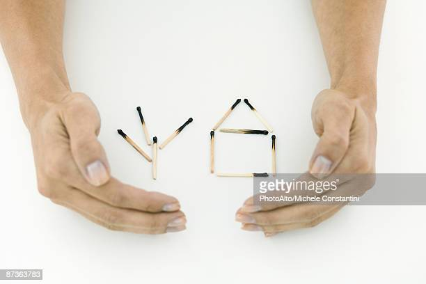 Hands protecting burnt matches arranged in shape of house and tree