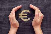 Hands protecting drawn euro sign on black chalkboard background. Close up.