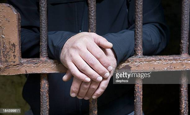 Hands protruding from jail cell bars