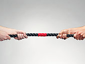 Hands pulling on rope during game of tug-of-war