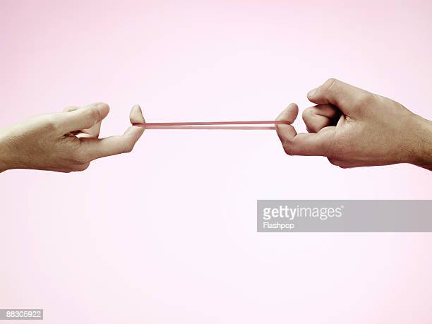 Hands pulling rubber band