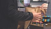 Hands putting burgers into bag. Man buys packaged food in a cafe.