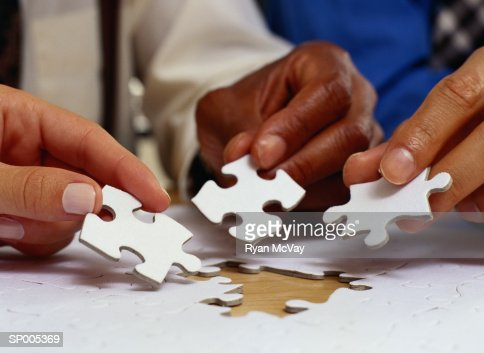 Hands Putting Jigsaw Puzzle Pieces in Place : Stock Photo