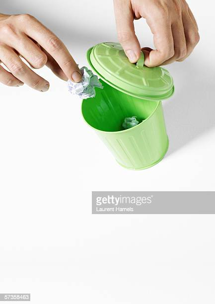 Hands putting trash in tiny trash can