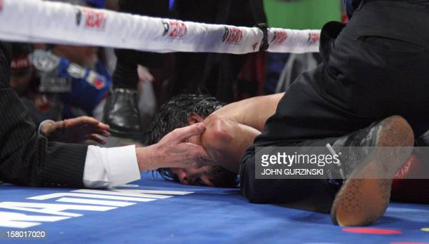 Hands reach in ringside to support the head of Manny Pacquiao after he was knocked out by Juan Manuel Marquez on December 8 at the MGM Grand Garden...