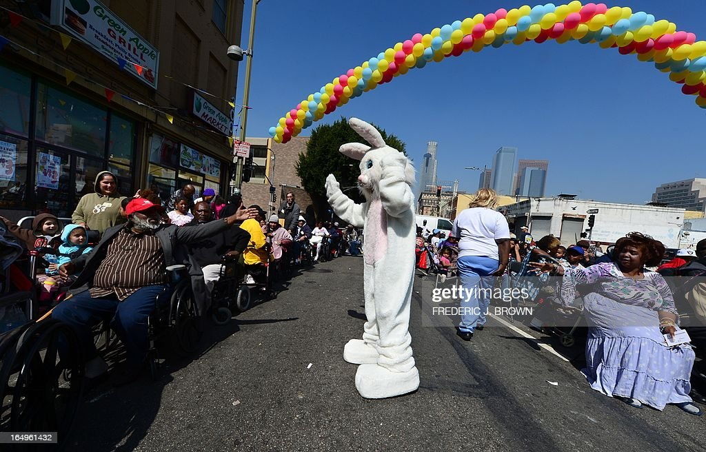 Hands reach out to touch a person dressed as the Easter Bunny as people attend the Los Angeles Mission's Good Friday event on Skid Row on March 29, 2013 in Los Angeles, California. Celebrities and volunteers joined together in giving something back to this community of the homeless, among the largest in the US, who were fed a fully-prepared meal and had the opportunity to be given foot washing and hygiene kits. Foot washing, a symbolic ritual of humbleness and respect derived from Jesus Christ's washing of his disciples feet at the Last Supper, was offered by the Los Angeles Health Center and volunteers. AFP PHOTO/Frederic J. BROWN