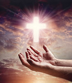 Hands reaching out with crucifix cross in sky concept for help, religion, salvation, forgiveness, assistance and love or begging