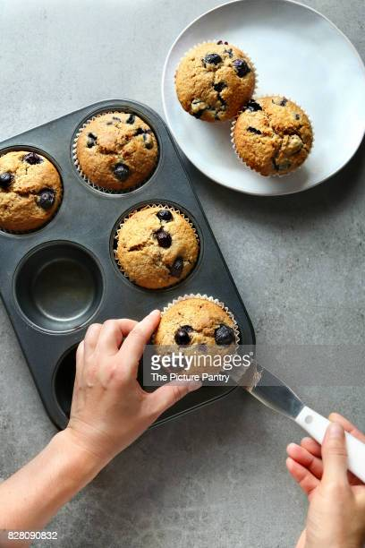 Hands removing a blueberry muffin from a baking pan.Top view