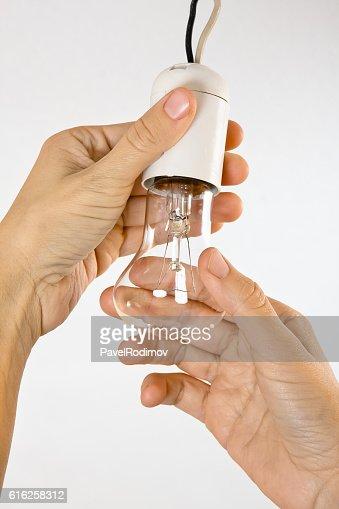 hands replacing incandescent light bulb : Foto de stock