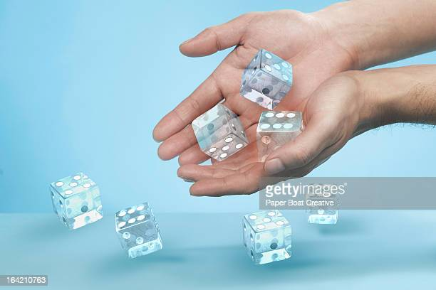 Hands rolling out glass dice on to a table