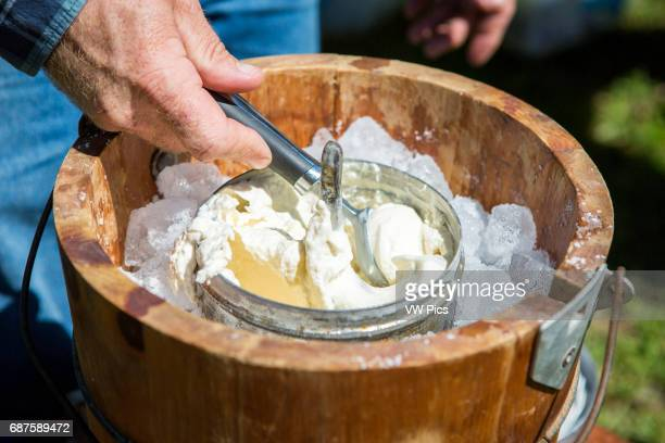 Hands scooping ice cream out of oldfashioned ice cream maker