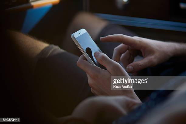 Hands scrolling on smartphone, inside car