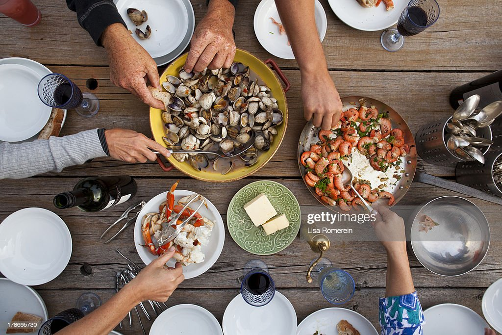 Hands serving shellfish meal around wooden table : Stock Photo