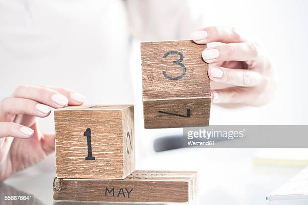 Hands setting the date on a wooden calendar