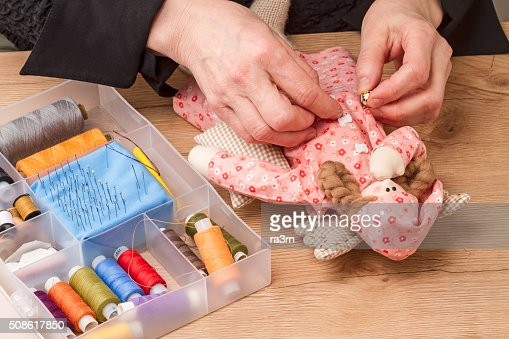 Hands sew on buttons for homemade doll : Stock Photo
