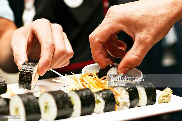 Hands sharing a sushi platter in Asian restaurant