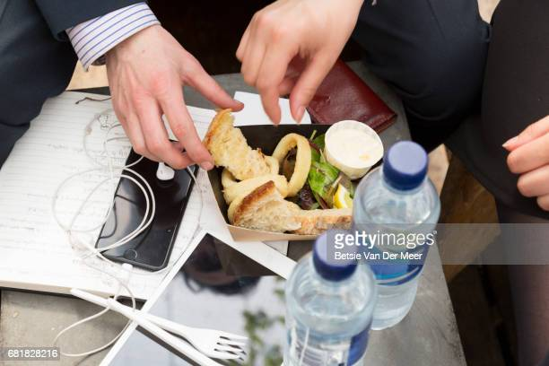 Hands sharing food dish surrounded by portable information devices.