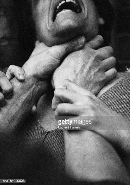 Hands strangling woman, close-up, b&w